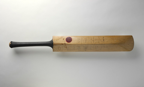 A cricket bat, photographed in a horizontal position against a plain white background. Its handle is to the left of the photo. The back of the bat is visible. The handle has a black rubber cover on it. The rubber has a small split in it at the end of the handle. There are signatures on the back of the bat. A circular red mark is visible near the upper right corner of the bat's back. The grain of the bat's timber can be seen running along the length of the bat.